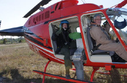 Prescribed burn team members in a helicopter.