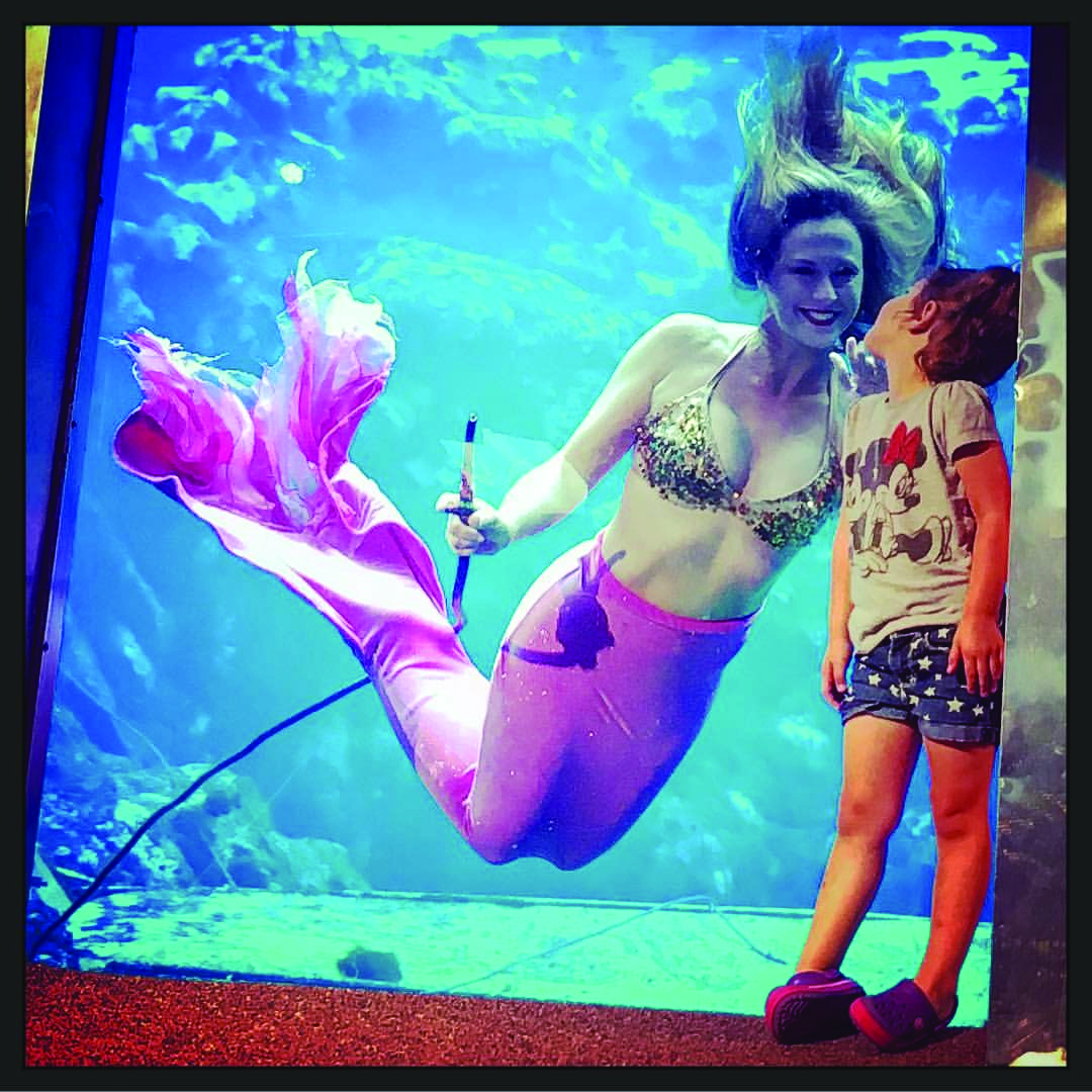 Weeki Wachee Mermaid entertaining a young girl