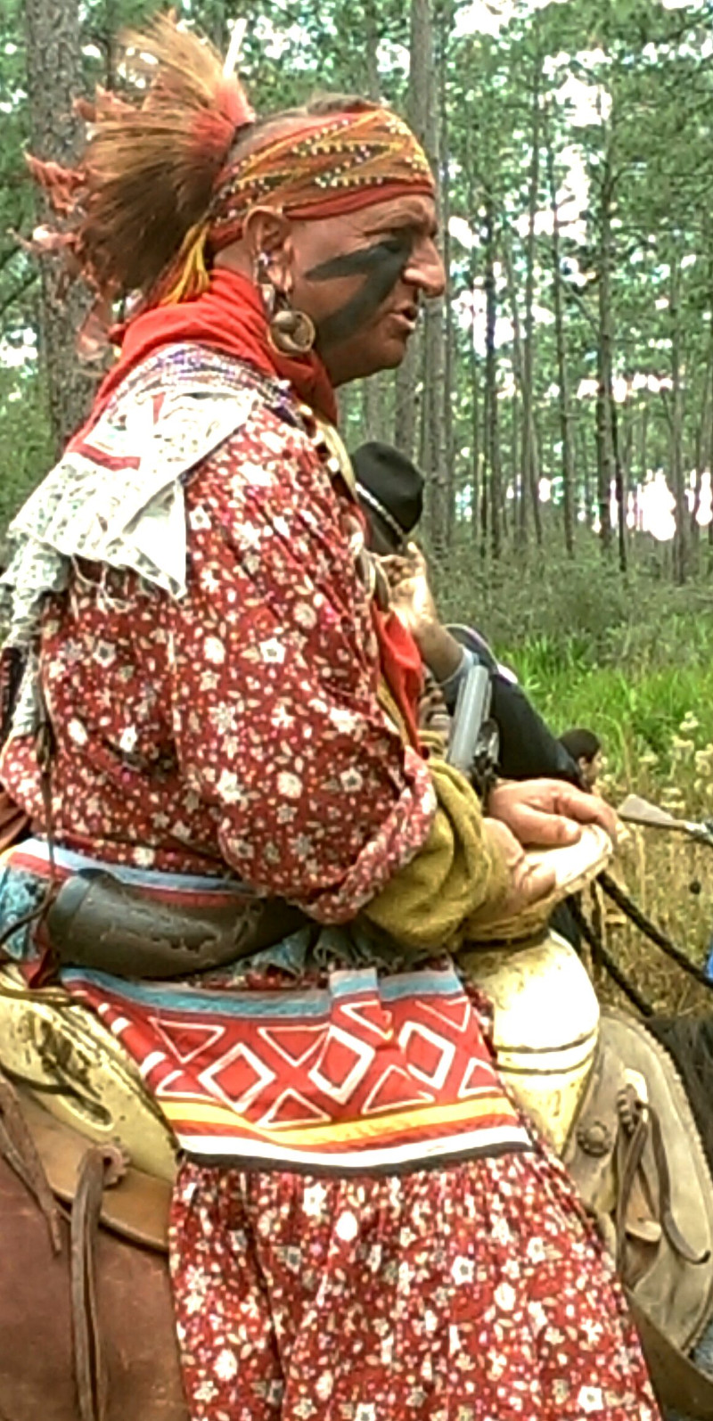 a seminole warrior reenactor in a colorful outfit rides a horse.