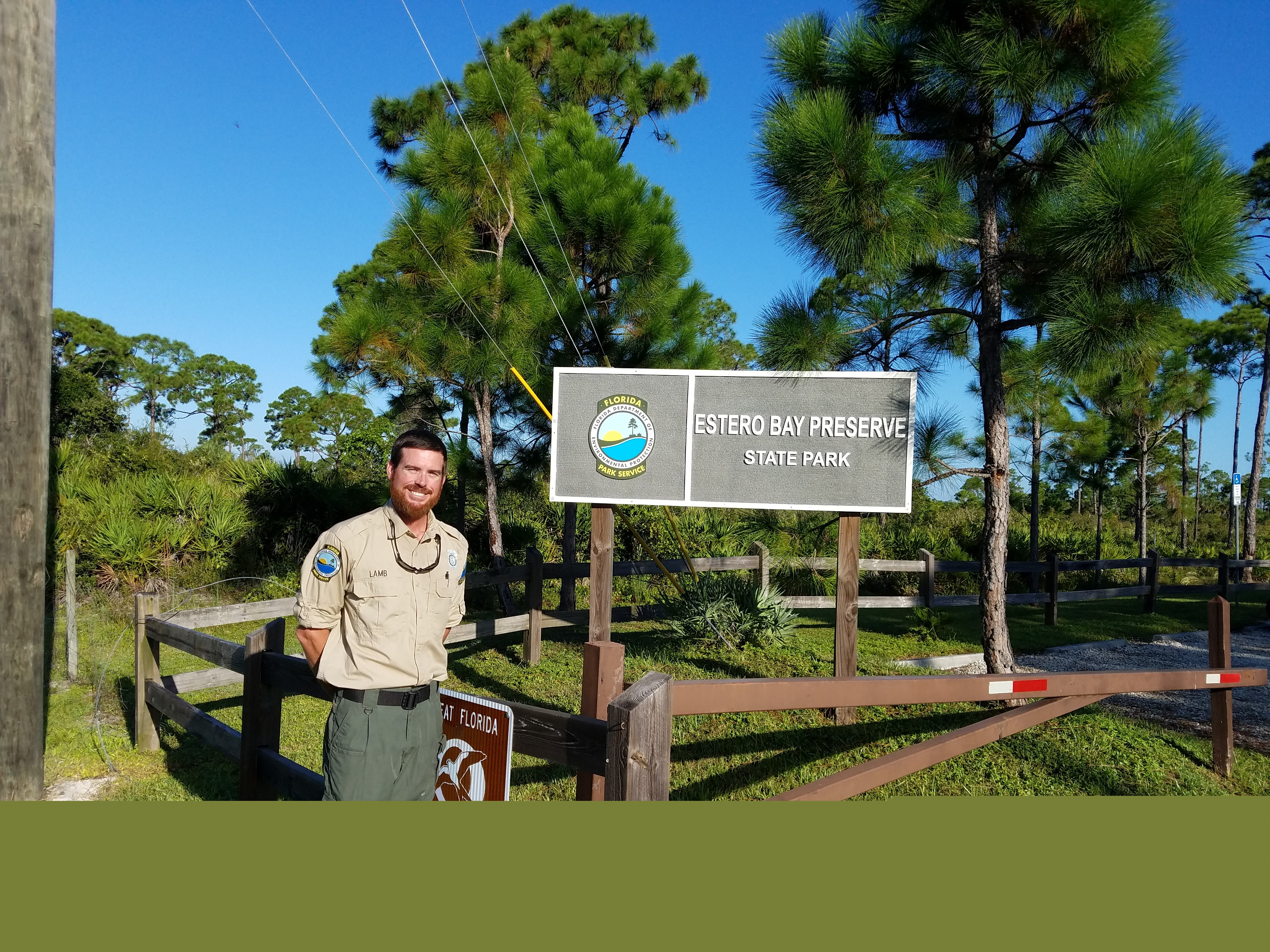 Justin Lamb poses with the park sign at Estero Bay Preserve State Park.