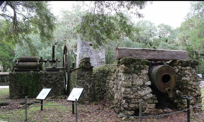 a path winds past a stone structure with iron boilers and interpretive signs