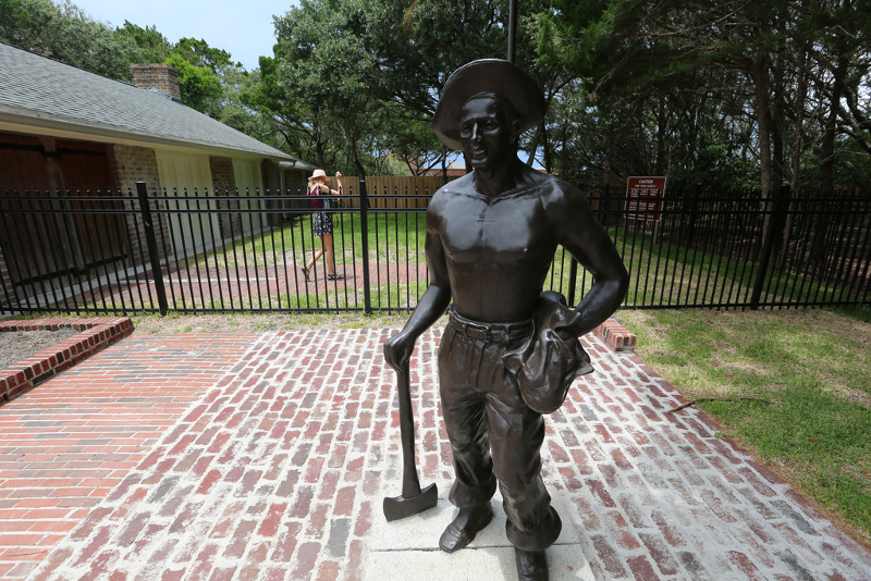 statue of a man standing with an ax outside iron gates at fort clinch.