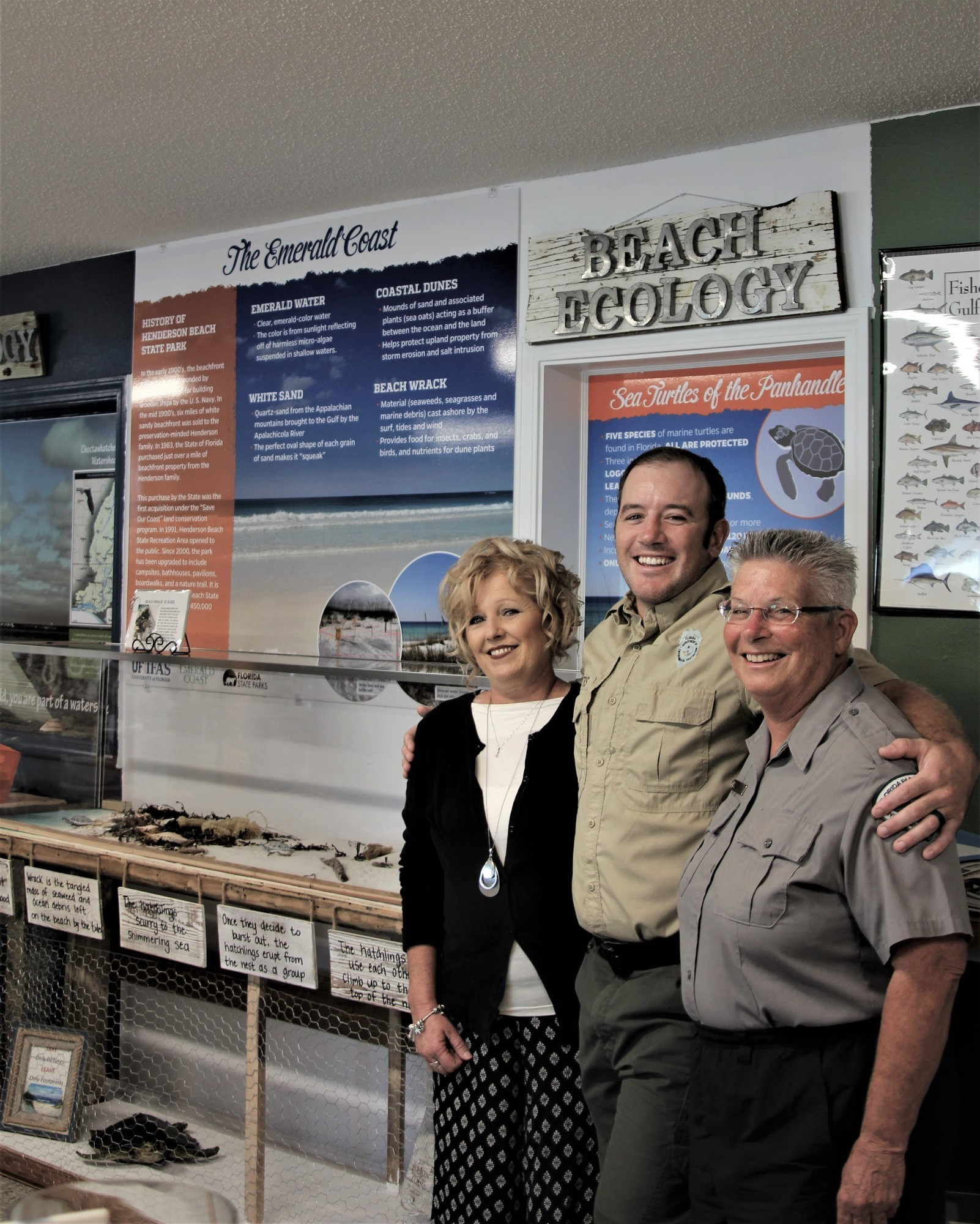 Volunteer Doe Schuster with park staff infront of sea turtle interpretive exhibit.