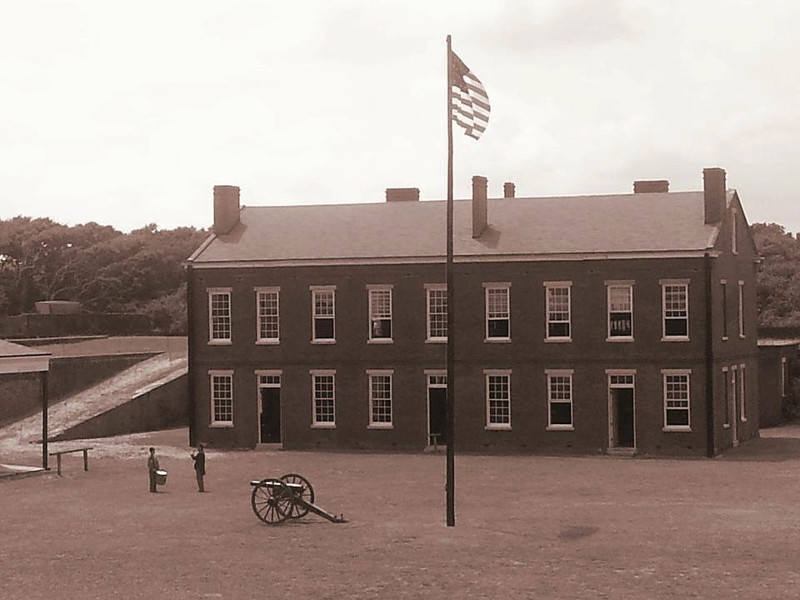 historic image of fort clinch depicting the main building with flagpole, cannon, and two soldiers.