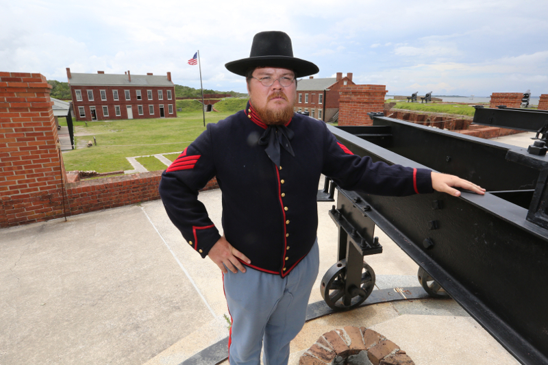 a man in union uniform stands atop the fort walls next to a cannon.