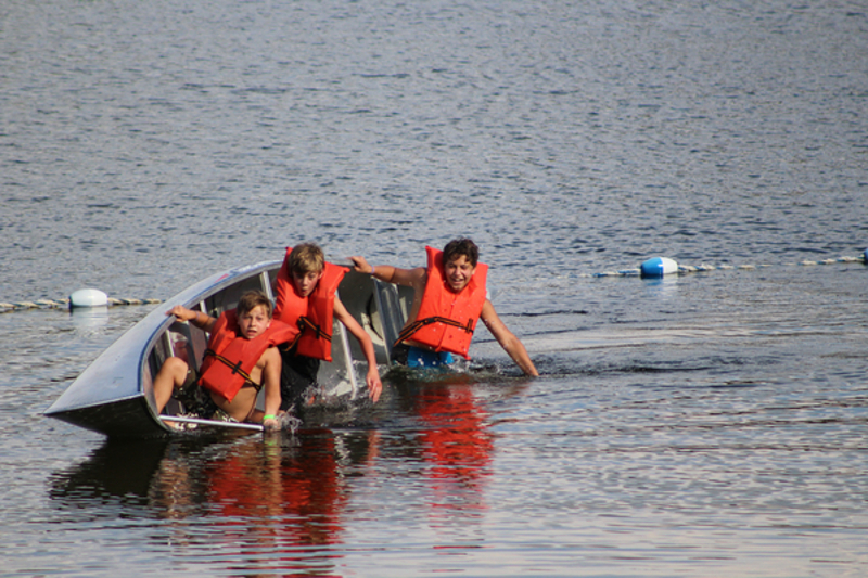 a canoe with three kids wearing bright orange PFD's tips over in the water