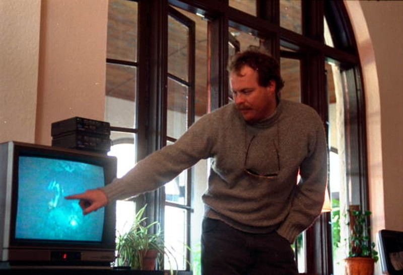 a man points to an image of a diver on a tv