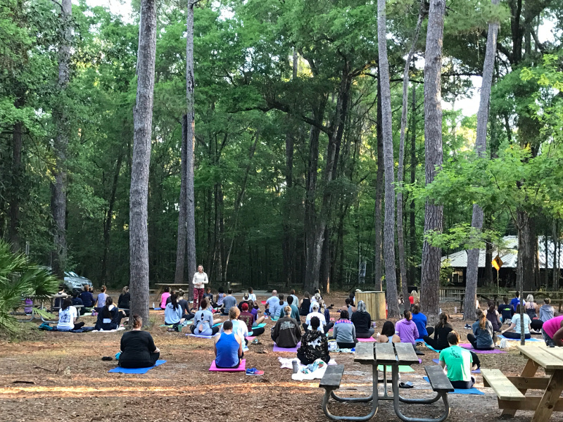 Visitors are seen sitting during a yoga program at Devil's Millhopper State Park.