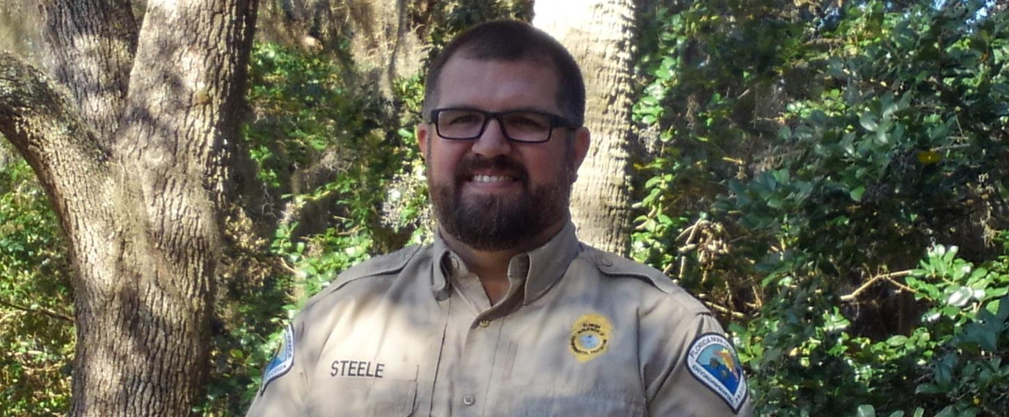 Park Manager Robert Steele stands under the shade of the trees.