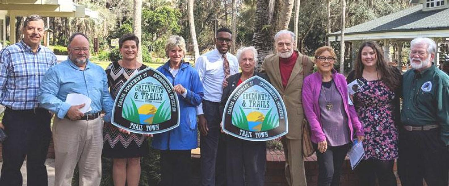 A group of people posing for a picture with their trail town plaque.