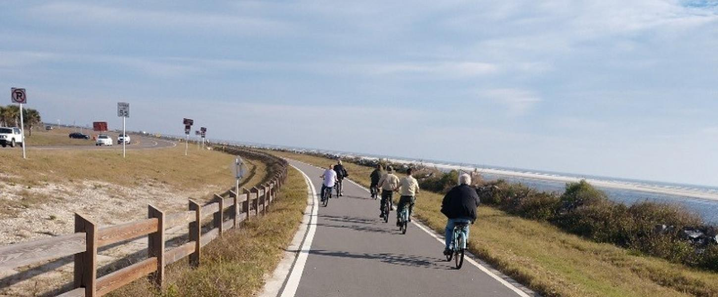 a group of bike riders pedal down a paved trail next to the coastline
