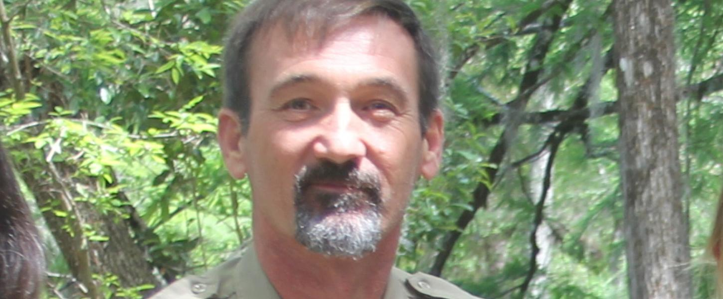 a man stands in front of trees in a park service uniform