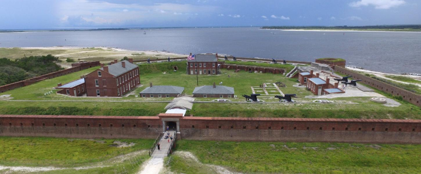 a fort with pentagonal brick walls and numerous building and guns against the backdrop of the ocean.
