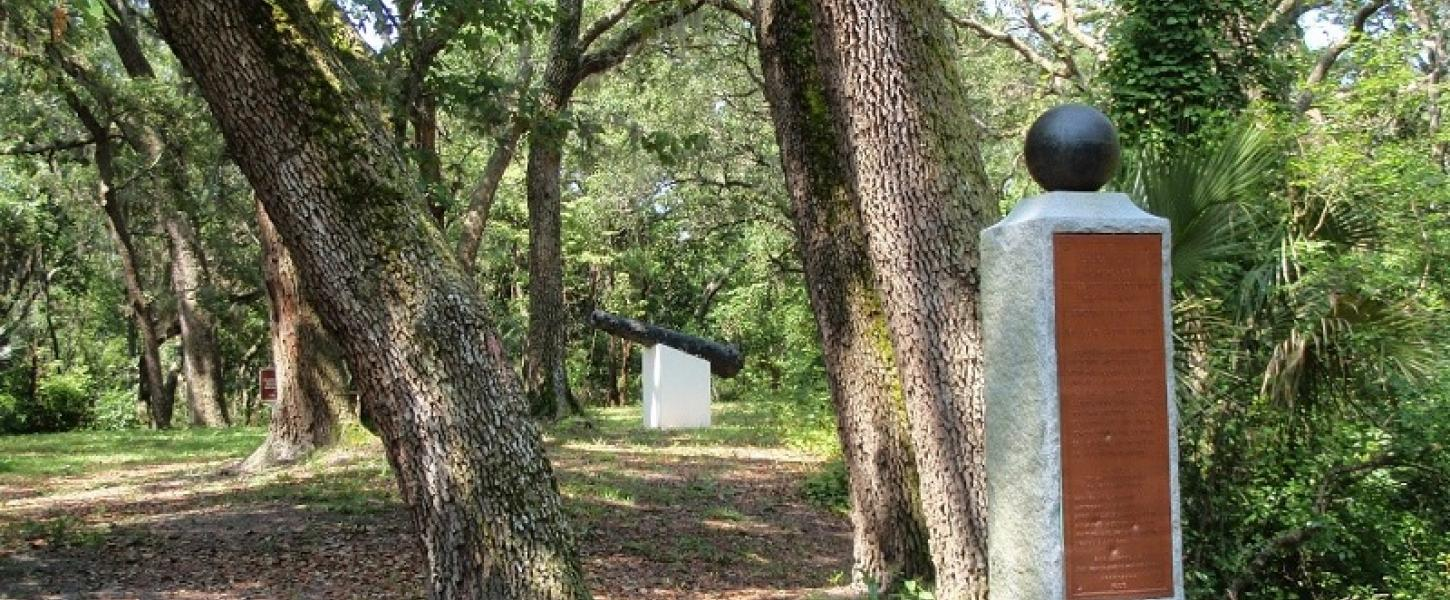 a monument, trees, and cannon at yellow bluff fort historic state park