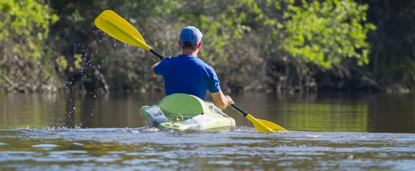 Man glides through water on green kayak.