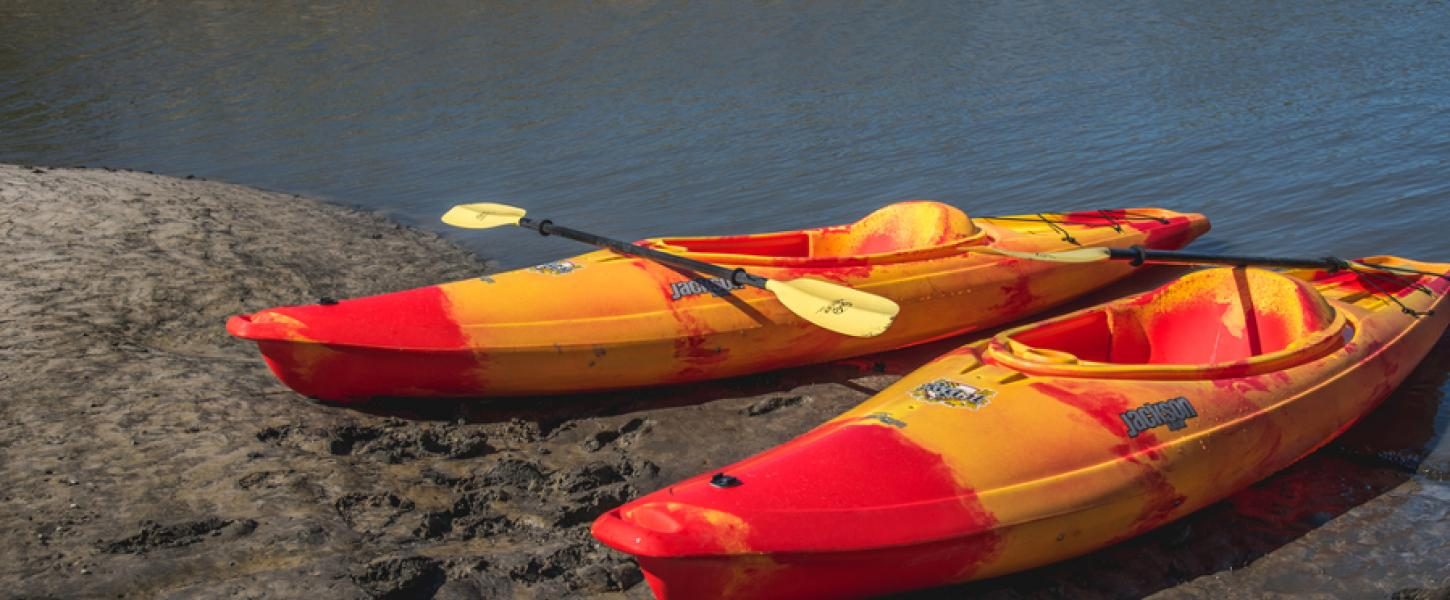 Two red and yellow kayaks rest in the sand at Little Talbot Island State Park.