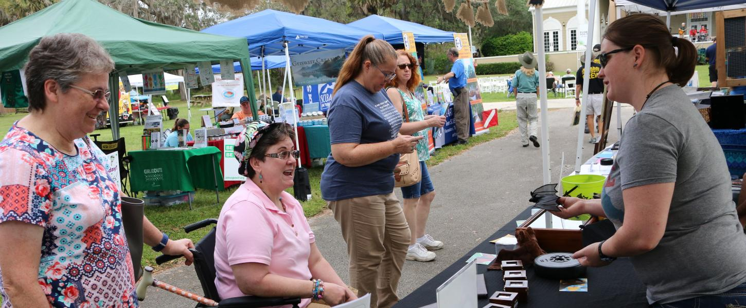 A state park volunteer at a booth, speaking with guests.