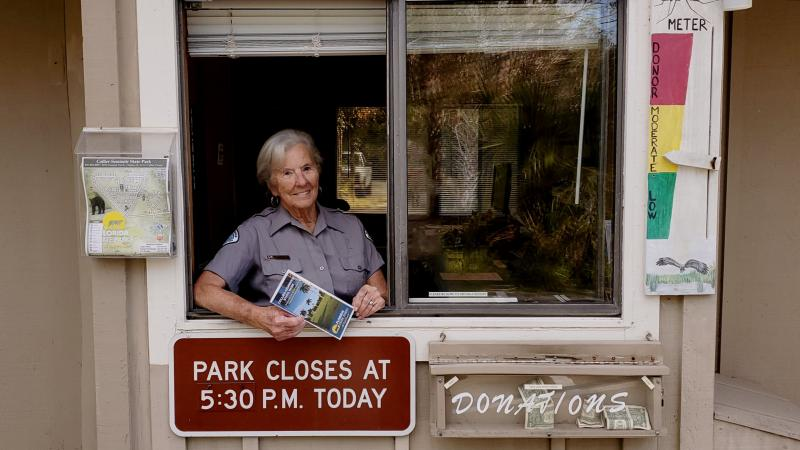 woman standing in a window smiling holding a brochure