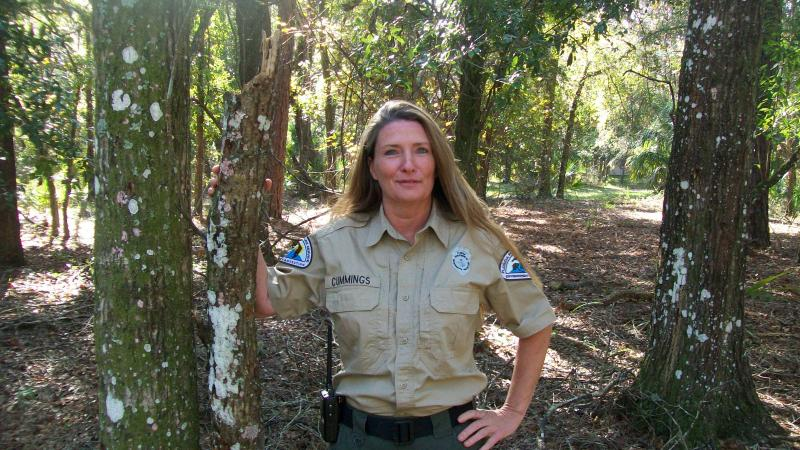 Park Ranger Jane Cummings in the forest smiling at the camera