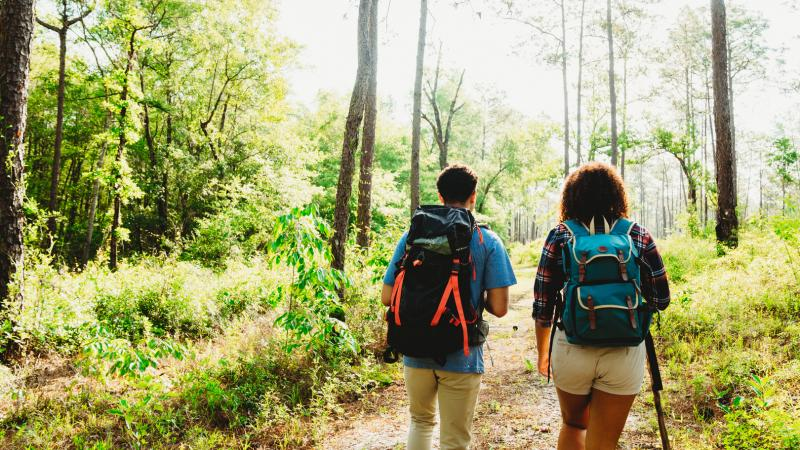 Two people with backs to camera and backpacks walk on a trail at Ponce de Leon Springs State Park.