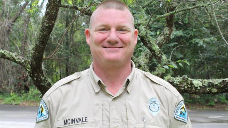 A man in a park service uniform smirks at the camera