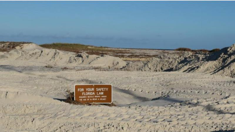 A view of the sand swept on shore by hurricane michael almost covering a sign.