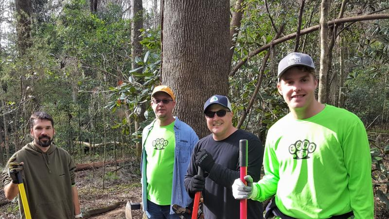A group of four TMBA trail work volunteers stand holding their equipment in a forest.