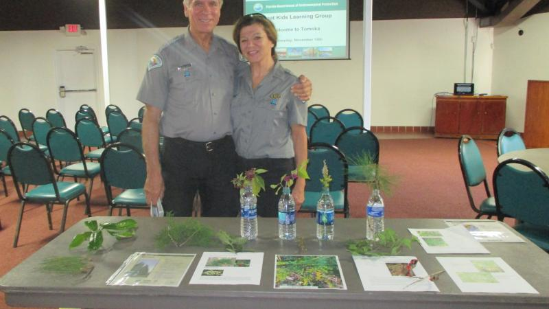 Volunteers Bruce and Darlene standing by a table with interpretive materials on it