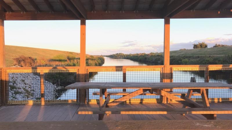 Wooden outlook that has wooden picnic tables during sunset