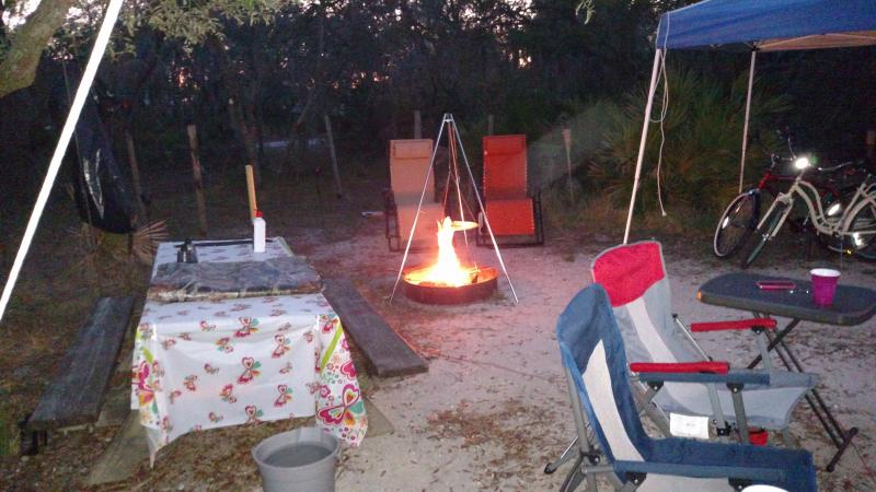 A view of a campsite with table, chairs and camp fire.