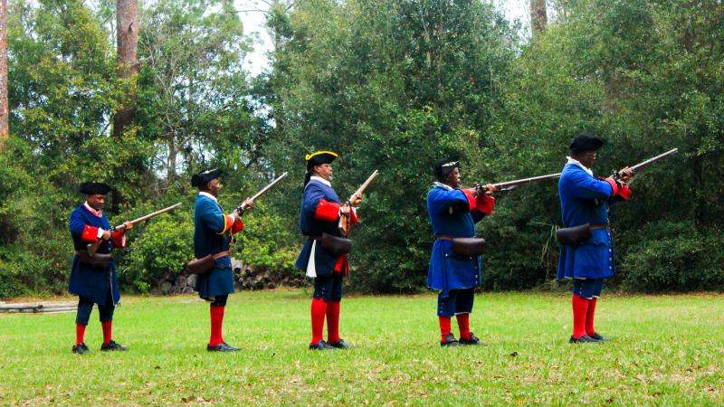 A line of 5 reenactors wearing blue and red historic costume prepare to fire muskets.