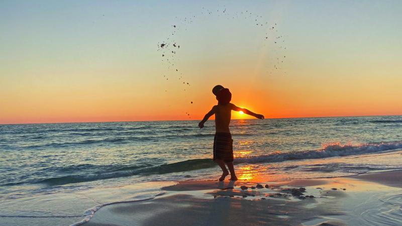 A boy plays by the shoreline at sunset.