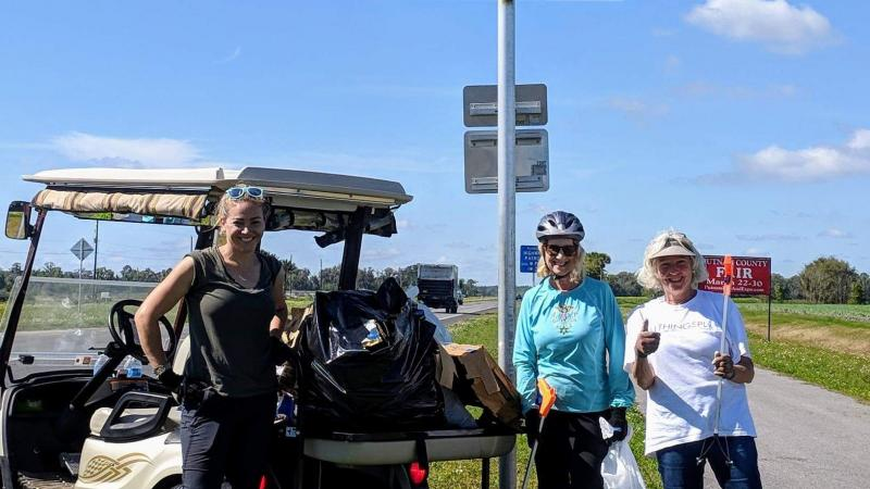Three women stand on a paved trail next to a sign and a golf cart holding trash bags.