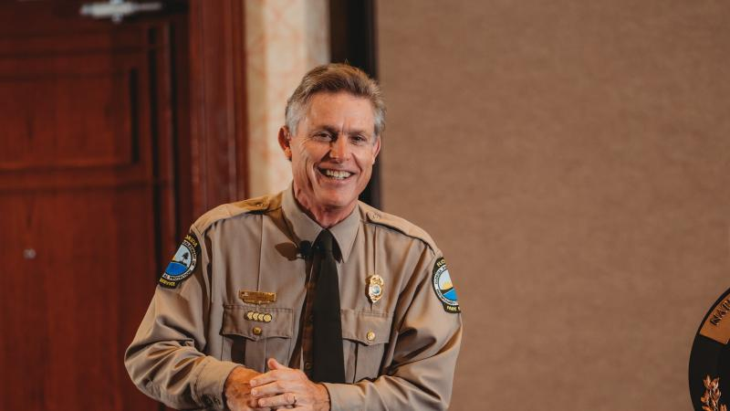 Florida Park Service Director Eric Draper, in Park Service uniform, clasps hands and smiles, indoors.