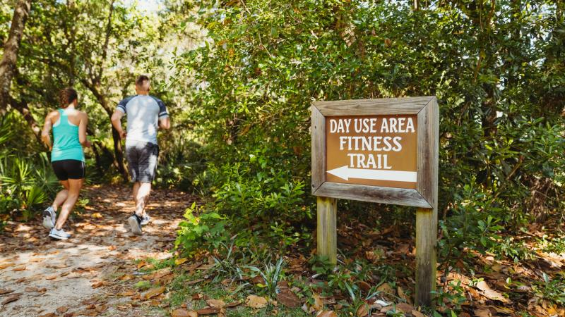 "Two people running on a forested trail on a sign that reads ""Day Use Fitness Trail."""