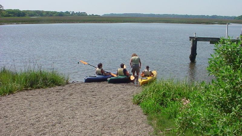 3 kayaks are launched into the water at a sandy ramp.