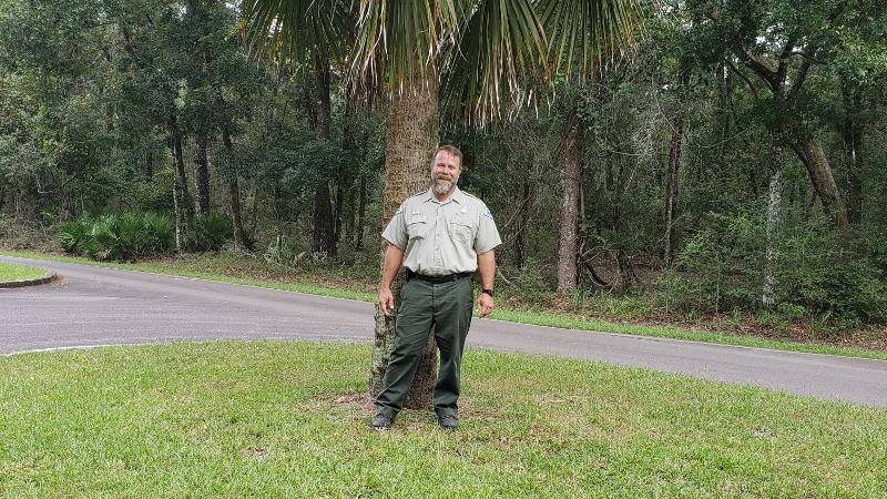 image of bryan summerlin, park ranger at manatee springs state park, standing outside in front of a palm tree.