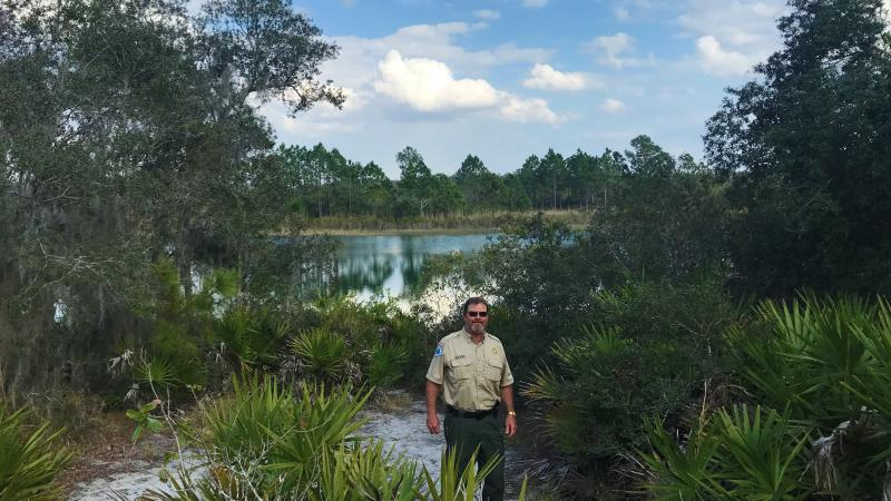 Park Manager Andy Noland standing at Catfish Creek surrounded by saw palmetto, oaks, and a lake behind him