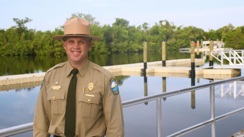 Man in park uniform standing near water and boat launch