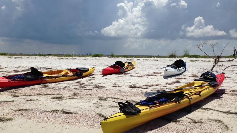 3 kayaks sitting on the shore of the beach.