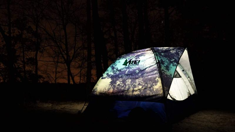 Tent is illuminated from inside surrounded by darkness.