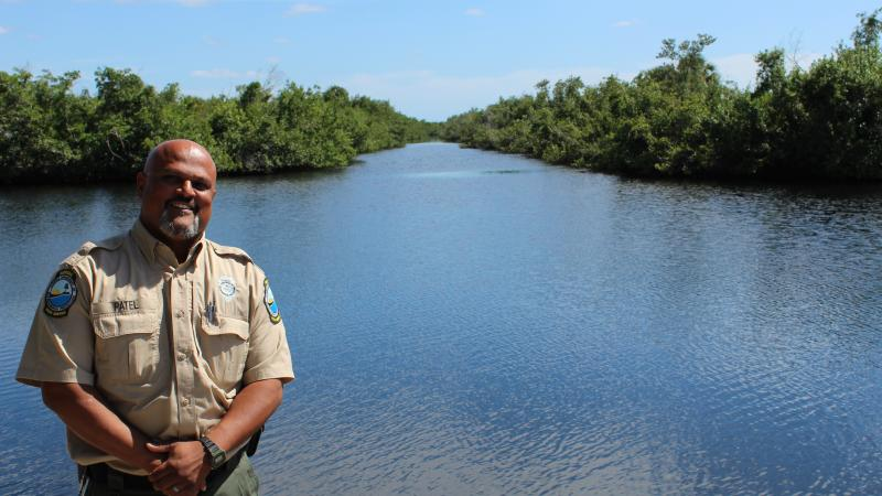 A male biologist in a Florida Park Service uniform stands proudly by a body of water.