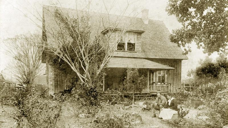 The Dudley farmhouse with Norman and Winnie sitting in front from 1915