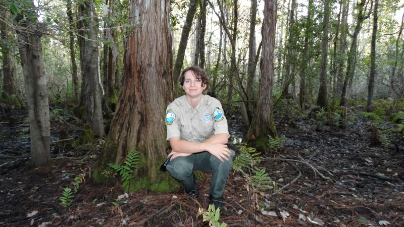 Park Ranger Jo smiling at the camera with cypress trees behind her