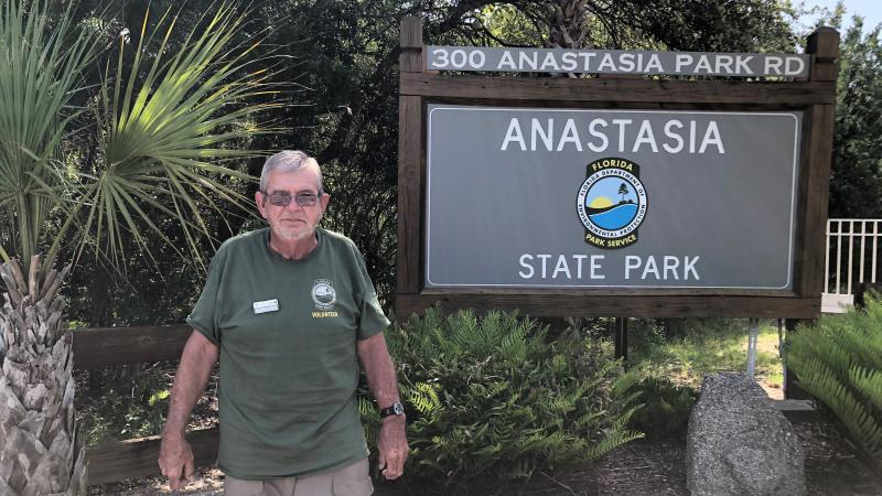 Anastasia State Park volunteer Darwin Matthews smiling for the camera with the Anastasia SP behind him