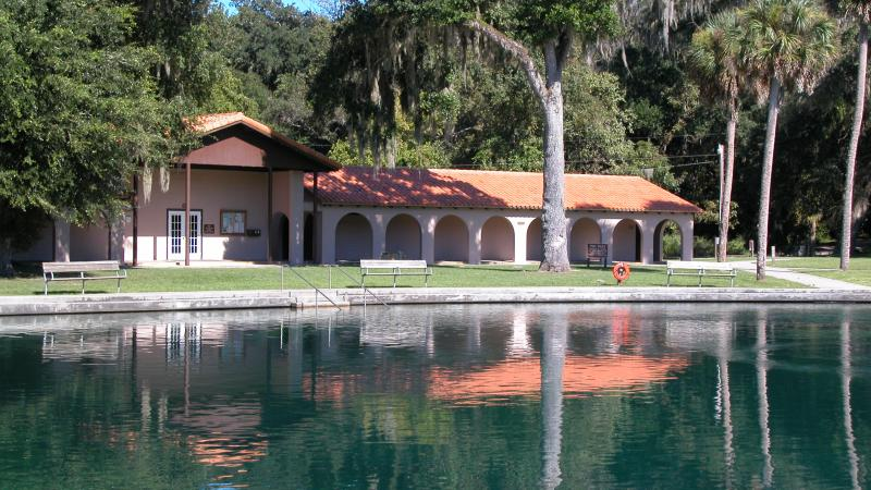 A view of the welcome center at de leon springs in front of the water.