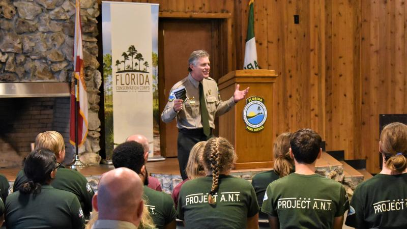 Florida Park Service Director speaks to Florida Conservation Corps graduates in wood-paneled room at Wekiwa Springs State Park