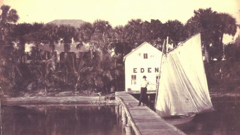 A boathouse and dock rest on the shoreline of the Indian River Lagoon.