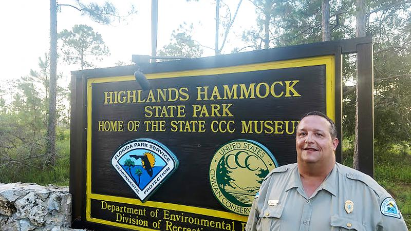 HHSP Manager Morgan Tyrone standing next to the park entrance sign