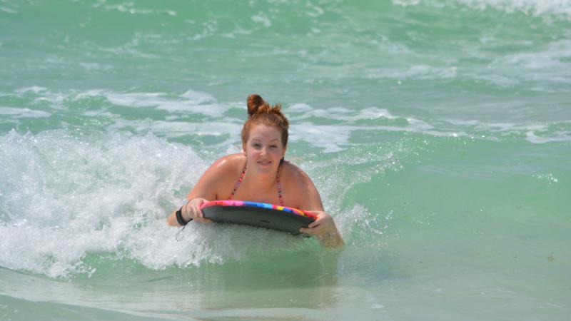 Young girl is all smiles as she glides on wave on her surfboard in emerald green waters.
